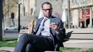 Businessman eating baguette and sitting on street bench with cellphone.