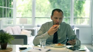 Businessman eating sandwich and looking on cellphone