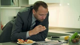 Businessman eating sandwich and reading newspaper, steadycam shot