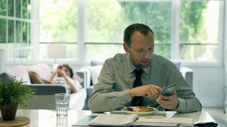 Businessman eating sandwich and working on documents