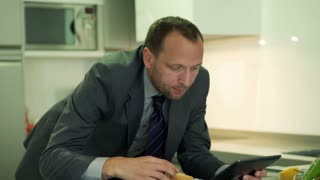 Businessman eating sandwich and working on tablet, steadycam shot