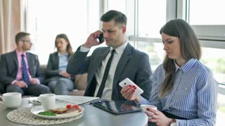Businessman having a call and businesswoman using cellphone