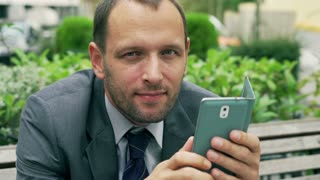 Businessman holding cellphone and smiling, closeup, steadycam shot