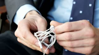 Businessman holding earphones and truing to untangle them, steadycam shot