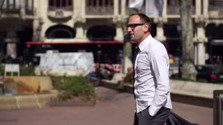 businessman holding his jakcet and walking along the street on a sunny day