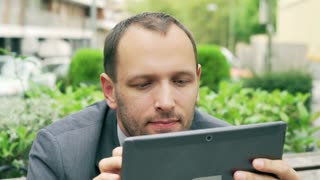 Businessman holding tablet and looking to the camera, steadycam shot