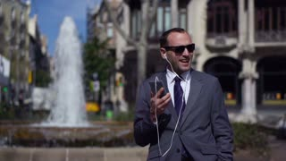 businessman listening music in front of fountain, slow motion shot at 240fps