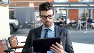 Businessman looking thoughtful while reading something on tablet, steadycam shot