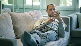 Businessman lying on the sofa and working on cellphone