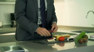Businessman making sandwich for breakfast, steadycam shot