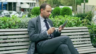 Businessman on the street bench using stylus to text on cellphone