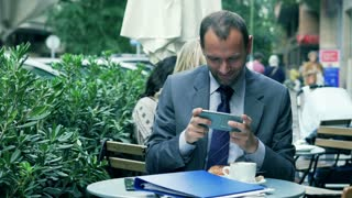 Businessman playing on smartphone in the street cafe