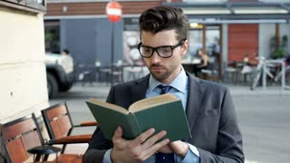 Businessman reading book and doing serious look to the camera, steadycam shot