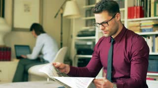 Businessman reading newspaper and woman working at home