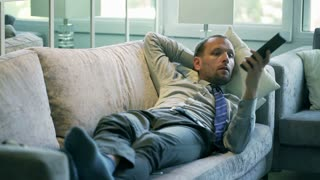 Businessman relaxing on the sofa and watching television