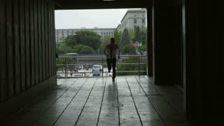 Businessman running through the passage, slow motion shot, steadycam shot