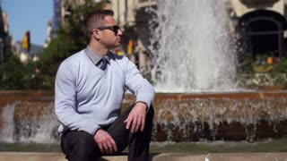 businessman sitting and relaxing by the fountain in the city, slow motion