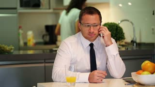 Businessman sitting at home and talking on cellphone