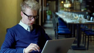 Businessman sitting in the restaurant and working on laptop