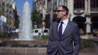 businessman standing in front of fountain in city, slow motion shot at 240fps