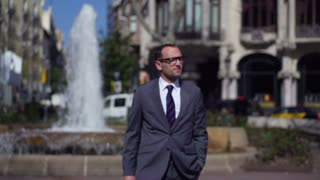 businessman standing in front of the fountain in the city, slow motion