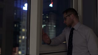 Businessman standing next to the window and doing serious look to the camera
