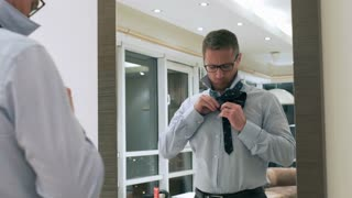 Businessman tie a tie in front of the mirror