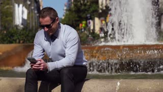 businessman using cellphone by the fountain, slow motion shot at 240fps