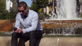 businessman using cellphone by the fountain, slow motion shot at 60fps