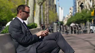 businessman using his cellphone on a bench in a city, slow motion shot at 60fps