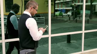 Businessman walking and texting on smartphone, steadycam shot