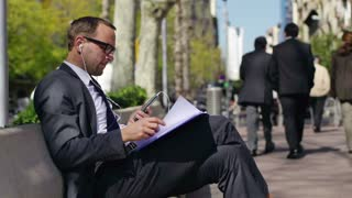 businessman with cellphone checking documents on bench in city, slow motion