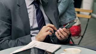 Businessman working on cellphone in the cafe, steadycam shot