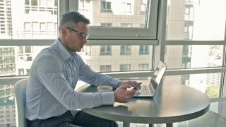 Businessman working on laptop and cellphone in the morning