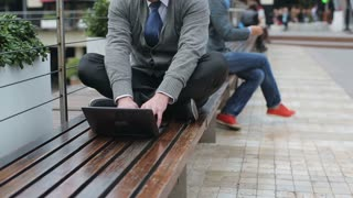 Businessman working on laptop and sitting on street bench, steadycam shot