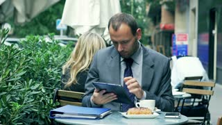 Businessman working on tablet in the street cafe