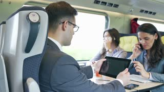 Businessman working on tablet in the train, steadycam shot