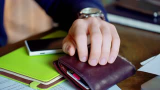 Businessman's hand holding wallet which lies on the table