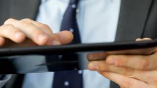 Businessman's hands browsing internet on tablet
