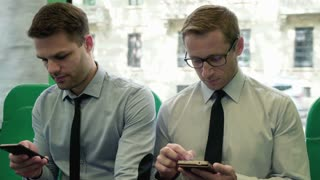 Businessmen riding in the bus and using smartphones, steadycam shot