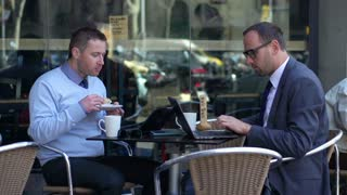 businessmen working on laptops and eating breakfast in cafe, slow motion