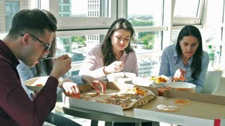 Businesspeople eating lunch together in the office