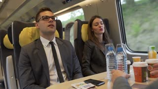 Businesspeople riding in the train and eating, steadycam shot
