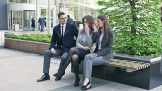 Businesspeople sitting on the bench and working together