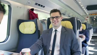 Businesspeople smiling to the camera in the train, steadycam shot