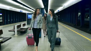 Businesspeople walking with luggage on the station, steadycam shot
