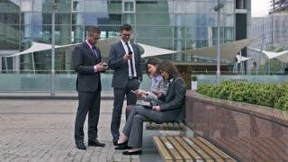 Businesspeople working on smartphones outdoors