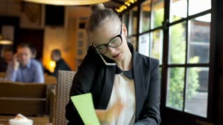 Businesswoman checking papers and speaking on cellphone in the cafe, steadycam s