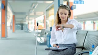 Businesswoman checking time and working on laptop while sitting on platform