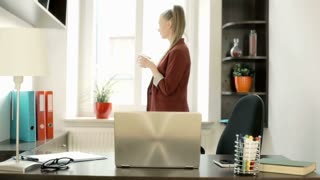 Businesswoman drinking coffee next to the window and sitting down by the desk, s